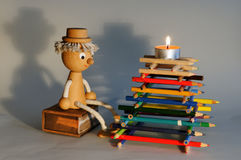 Wooden figurine by the bonfire made of color pencils Royalty Free Stock Photography