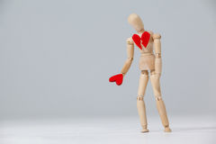 Wooden figurine with a broken heart and holding a red heart stock image