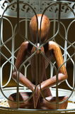 Wooden figurine in a cage Royalty Free Stock Photography