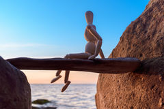 Wooden figurine at the coast Stock Photos