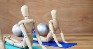 Wooden figurine exercising on exercise mat stock footage
