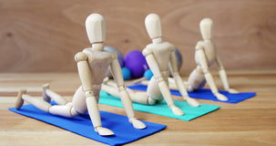 Wooden figurine exercising on exercise mat. Against wooden background stock video