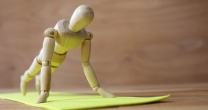 Wooden figurine exercising on exercise mat. Against wooden background stock footage