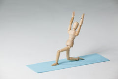 Wooden figurine exercising on exercise mat Stock Photos