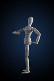 Wooden figurine flexing muscles in bodybuilder pose on dark back Royalty Free Stock Image