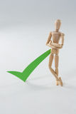 Wooden figurine with green check mark Stock Photos