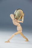 Wooden figurine holding a gold coin Royalty Free Stock Photos