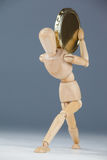 Wooden figurine holding a gold coin Stock Photos