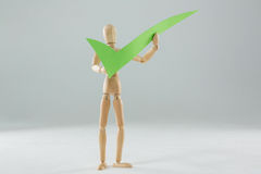 Wooden figurine holding a tick sign. Against white background stock photo