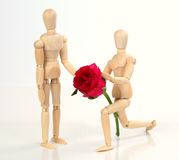 Wooden figurine man holding and giving rose Stock Photography