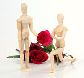Wooden figurine man holding and giving rose to lover with rose b Royalty Free Stock Photography