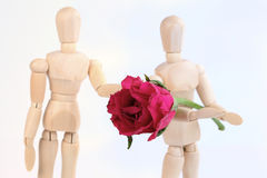 Wooden figurine man holding rose to lover. Stock Photo