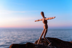 Wooden figurine. Wooden man stands on the top of sea boulder Stock Images