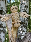 Wooden figurine of an owl. In the background of trunks of birches Stock Images