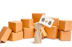A wooden figurine of a person stands near a pile of boxes and raises the question of how to transport the goods from one house stock photos