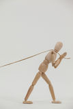 Wooden figurine pulling a rope Royalty Free Stock Photo