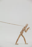 Wooden figurine pulling a rope Stock Photo