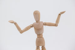 Wooden figurine standing with arms spread. Against white background Stock Images