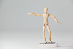 Wooden figurine standing with arms spread on a mouse Stock Photos