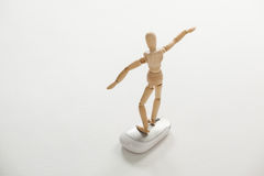 Wooden figurine standing with arms spread on a mouse Stock Photography