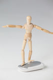 Wooden figurine standing with arms spread on a mouse Stock Photo