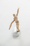 Wooden figurine standing with arms spread on a mouse Stock Image
