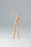 Wooden figurine standing with hand raised Royalty Free Stock Image
