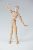 Wooden figurine standing with hand raised Royalty Free Stock Images