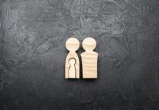 Wooden figurines of parents with the shape of a child inside the woman`s body on a concrete gray background. stock photos