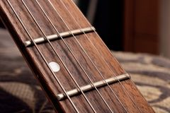 Wooden fingerboard of the guitar and strings close up. Macro royalty free stock image