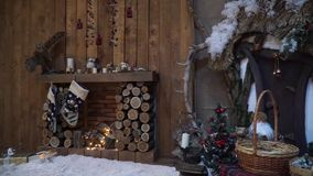 Wooden fireplace near the fairy doors. Wooden fireplace with twinkling fairy garlands near the door stock video