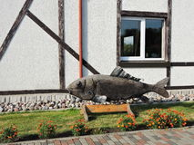 Wooden fish statue near home. Carved wooden fish near house, Lithuania Royalty Free Stock Photography