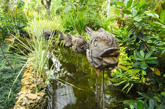 Wooden fish on a stick as a decoration in a chanel in the park a. Mong tropical green plants Royalty Free Stock Photo