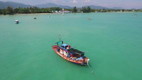 Wooden fisherman boat aerial slowmotion HD overflight. Traditional thai sailboat in clear blue water. Phuket, Thailand. stock video footage