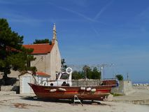 A wooden fisherman boat ashore on Premuda. The Krijal church with the graveyard situated at the harbor of the little island Premuda in the northern Adriatic sea royalty free stock photography