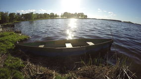 Wooden fishing boat on lake water in spring evening.Timelapse 4K stock video