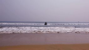 Wooden fishing boat landing on the beach. Ship arriving to shore. fisherman
