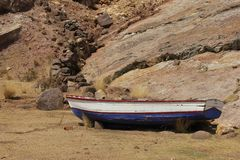 A wooden fishing boat on the shores. A wooden fishing boat lays on the shores on the island of Taquile in Lake Tititcaca, Peru royalty free stock image