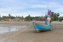 Wooden fishing boat on the  low tide beach. Stock Photo