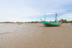 Wooden fishing boat on the  low tide beach. Stock Photos