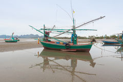 Wooden fishing boat on the  low tide beach. Stock Photography
