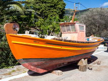 Wooden Fishing Boat Painting. Wooden fishing boat, caique, clinker, out of water for spring maintenance and re-painting, new coat of orange marine paint royalty free stock image