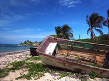 Wooden fishing boat rotting on beach with hotel in background No. Old wooden fishing boat rotting on beach with hotel in background North End Big Corn Island Royalty Free Stock Image