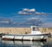 A wooden fishing boat in a small port stock image