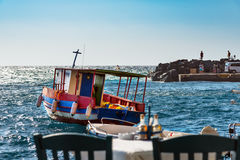 Wooden fishing boat at waves of harbor at Oia town, Santorini island, Greece Royalty Free Stock Image