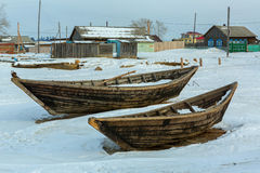 Wooden fishing boat on the winter snow-covered coast. Stock Photography
