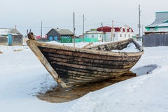 Wooden fishing boat on the winter snow-covered coast. Royalty Free Stock Photo