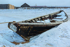 Wooden fishing boat on the winter snow-covered coast. Stock Images