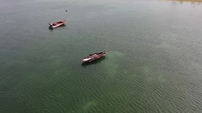 Wooden fishing boats anchored in the sea. Top view from drone stock footage