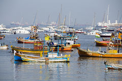 Wooden fishing boats and expensive yachts on the sea water near the city of Mumbai, India. MUMBAI, INDIA - JANUARY 29, 2017 : Wooden fishing boats and expensive Stock Photography
